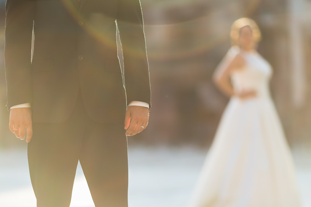 Primer plano manos novio, novia desenfocado al fondo