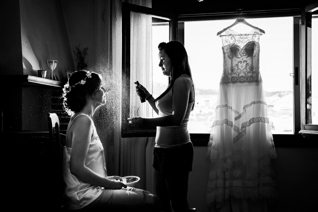 Novia maquillándose con traje colgado de la ventana