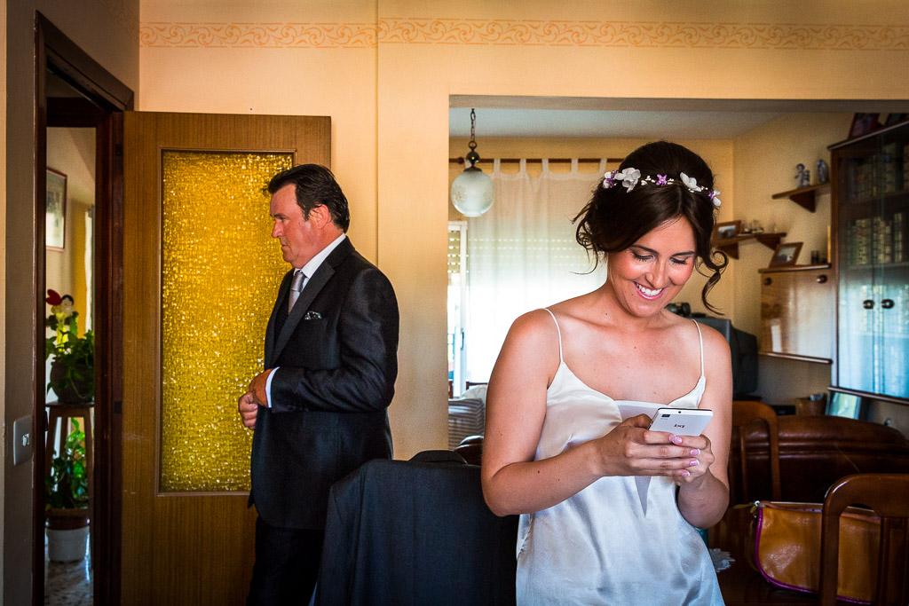 Novia esperando vestirse, usando el móvil