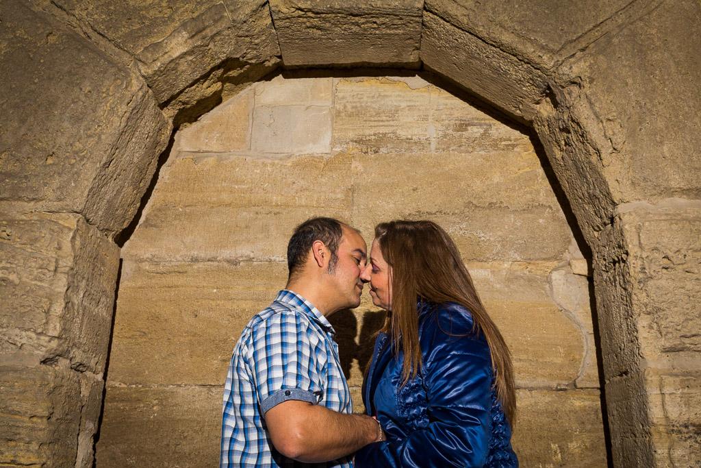 Pareja besándose debajo de un arco en la plaza la Seo