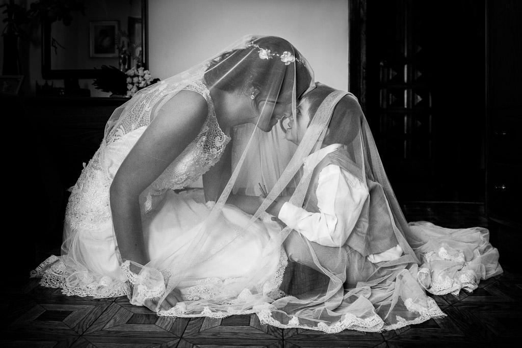 Novia cubriendo con el velo a su sobrino
