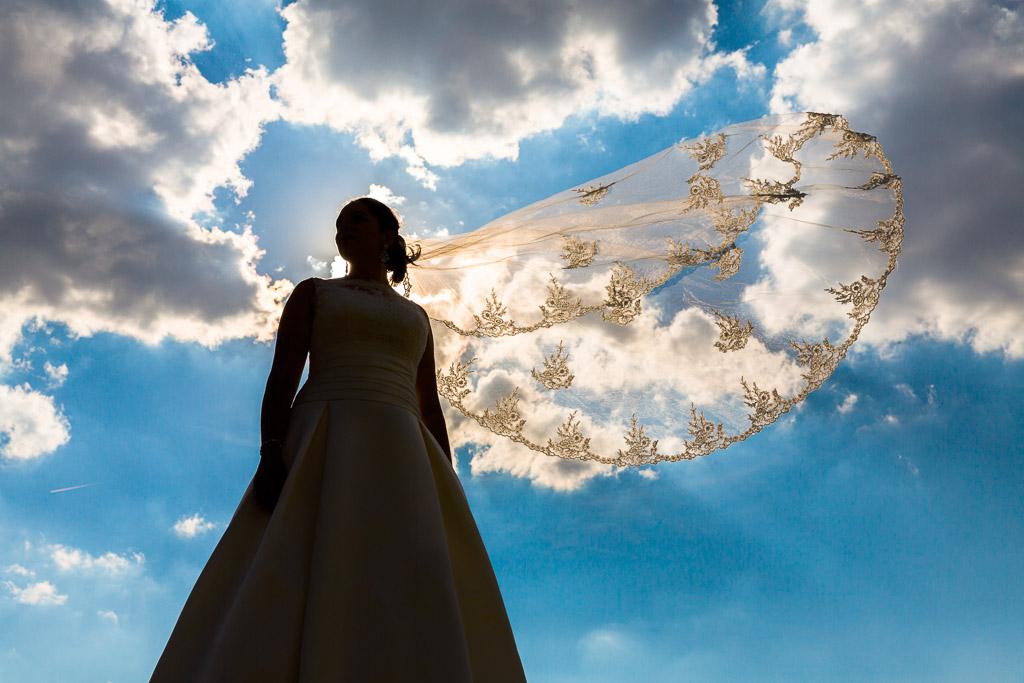 Novia a contraluz con el velo al viento
