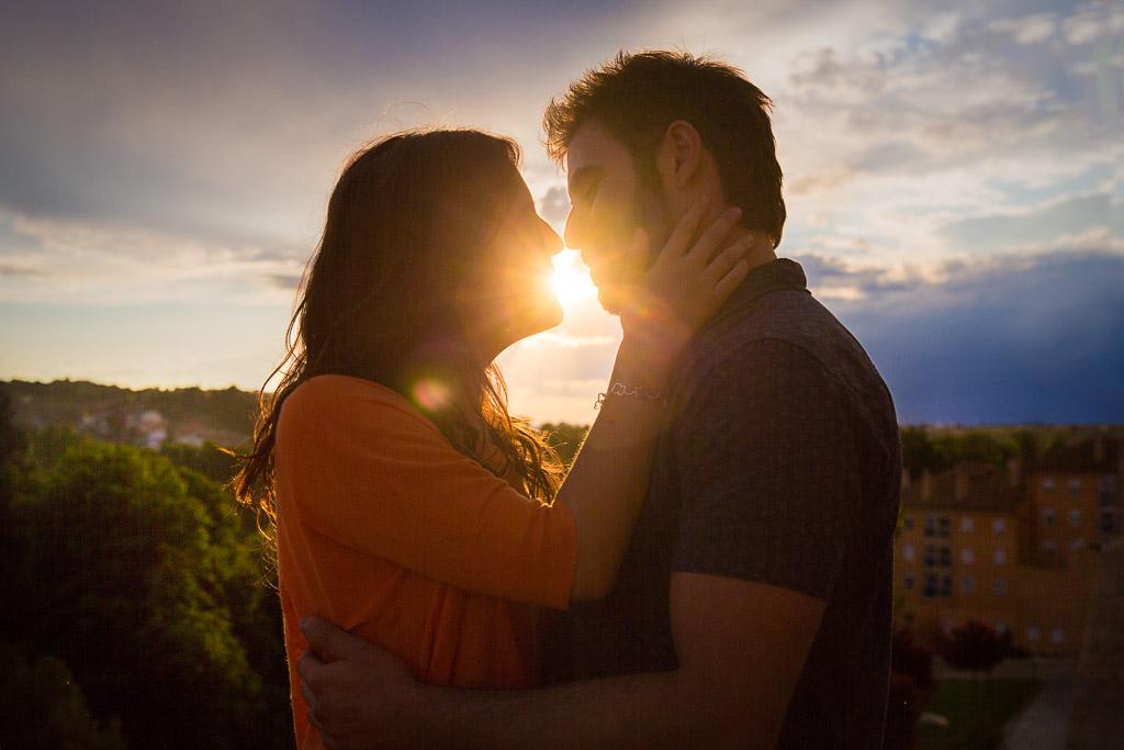Puesta de sol con en medio del beso de una pareja.